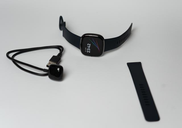 Neben der Uhr gibt es eine längeres Armband gratis dazu und das neue, clevere Ladegerät. Einen Stecker dafür gibt es leider nicht.